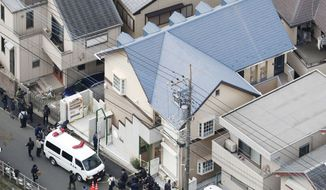 This aerial photo shows the apartment, center, where police found dismembered bodies in coolers in Zama city, southwest of Tokyo, Tuesday, Oct. 31, 2017.  A police spokesman said Tuesday the 27-year-old suspect confessed to cutting up the bodies and hiding them in cold-storage cases, covered with cat litter. (Kyodo News via AP)