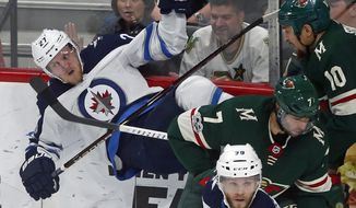 Winnipeg Jets' Nikolaj Ehlers, left, of Denmark, gets upended along the boards by Minnesota Wild's Chris Stewart, right, during the second period of an NHL hockey game Tuesday, Oct. 31, 2017, in St. Paul, Minn. (AP Photo/Jim Mone)