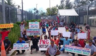 In this undated photo released by Refugee Action Coalition, refugees and asylum seekers hold up banners during a protest at the Manus Island immigration detention centre in Papua New Guinea. As Australia moved to close a detention center for asylum seekers it won't allow on its shores, Papua New Guinea's government warned the 600 men who want to stay at the Manus Island facility they may be removed if they stay beyond a Tuesday, Oct. 31, 2017 deadline. (Refugee Action Coalition via AP)
