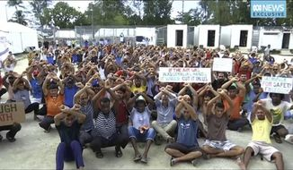 This photo made from Australia Broadcasting Corporation video taken on Tuesday, Oct. 31, 2017, shows asylum seekers protesting the possible closure of their detention center on Manus Island, Paua New Guinea. Lawyers for 606 asylum seekers in an Australian offshore detention center on Papua New Guinea's Manus Island sought a court injunction to prevent the facility's scheduled closure, as fears mounted of violent confrontations with locals who oppose the asylum seekers living among them. (Australia Broadcasting Corporation via AP)