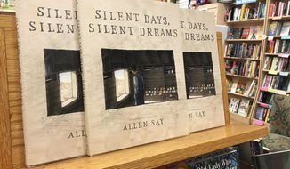 "In this Tuesday, Oct. 31, 2017 photo, copies of Allen Say's ""Silent Days, Silent Dreams"" sit on a bookshelf at a store in Boise, Idaho. The fictional biography of self-taught Idaho artist James Castle went on sale Tuesday after a federal judge ruled Monday that the award-winning children's book author from Oregon who created it likely didn't violate copyright laws. (AP Photo/Keith Ridler)"
