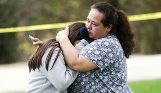 Maria Ortiz consoles her 5th-grade daughter, Crystal Godinez, after she was released from evacuation at Castle View Elementary School in Riverside, Calif., on Tuesday, Oct. 31, 2017. School officials say all students are accounted for as a man continues to hold someone hostage inside a Southern California elementary school.  (Watchara Phomicinda/The Press-Enterprise via AP)