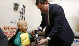 Arizona Republican Gov. Doug Ducey, right, hands out a bag of Halloween candy as he visits with a patient at Phoenix Children's Hospital Tuesday, Oct. 31, 2017, in Phoenix. Ducey spent time with children and their parents during Tuesday's hospital visit, and passed out candy and books to children undergoing treatment and read a Halloween-themed book. (AP Photo/Ross D. Franklin)