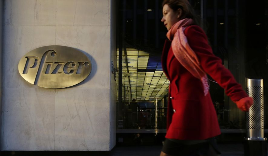 FILE - In this Monday, Nov. 23, 2015, file photo, a woman passes Pfizer's world headquarters in New York. Pfizer Inc. reports earnings Tuesday, Oct. 31, 2017. (AP Photo/Mark Lennihan, File)