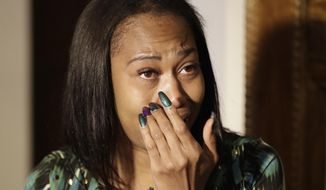 Erica Bailey, daughter of Aaron Bailey, wipes a tear during a news conference, Oct. 31, 2017, in Indianapolis. Two Indianapolis police officers won't face criminal charges for the June shooting death of Aaron Bailey, who crashed his car while fleeing from a traffic stop, a special prosecutor announced Tuesday. (AP Photo/Darron Cummings)