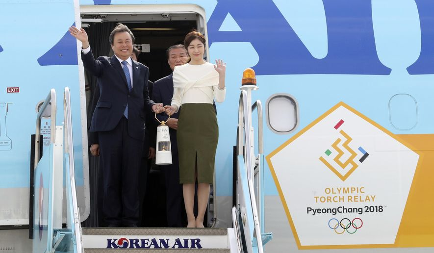South Korean Minister of Culture, Sports and Tourism Do Jong-whan, left, and former South Korean Olympic figure skating champion Yuna Kim, hold the Olympic flame upon arrival at Incheon International Airport in Incheon, South Korea, Wednesday, Nov. 1, 2017. (AP Photo/Lee Jin-man)