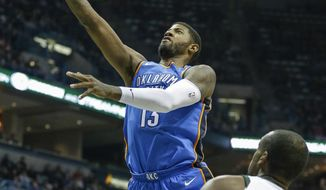 Oklahoma City Thunder's Paul George puts up a shot as Milwaukee Bucks' Khris Middleton looks on during the first half of an NBA basketball game Tuesday, Oct. 31, 2017, in Milwaukee. (AP Photo/Tom Lynn)