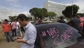 Uber drivers gather outside the Brazilian Congress to protest a bill aimed at regulating ride-sharing apps, that the Senate is expected to take up Tuesday, Oct. 31, 2017, in Brasilia, Brazil. The lower house of Congress has passed a bill that would require municipal governments to regulate ride-sharing apps like Uber. (AP Photo/Eraldo Peres)