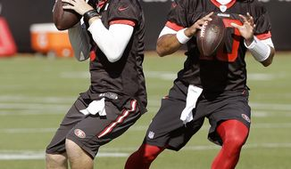 San Francisco 49ers quarterbacks C.J. Beathard, left, and Jimmy Garoppolo throw during a practice at the team's NFL training facility in Santa Clara, Calif., Wednesday, Nov. 1, 2017. (AP Photo/Jeff Chiu)