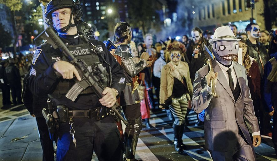 Heavily armed police guard as revelers march during the Greenwich Village Halloween Parade, Tuesday, Oct. 31, 2017, in New York. New York City's always-surreal Halloween parade marched on Tuesday evening under the shadow of real fear, hours after a truck attack killed several people on a busy city bike path in what authorities called an act of terror. (AP Photo/Andres Kudacki)