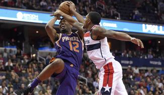 Phoenix Suns forward TJ Warren (12) is fouled by Washington Wizards guard Bradley Beal, right, during the second half of an NBA basketball game, Wednesday, Nov. 1, 2017, in Washington. The Suns won 122-116. (AP Photo/Nick Wass)