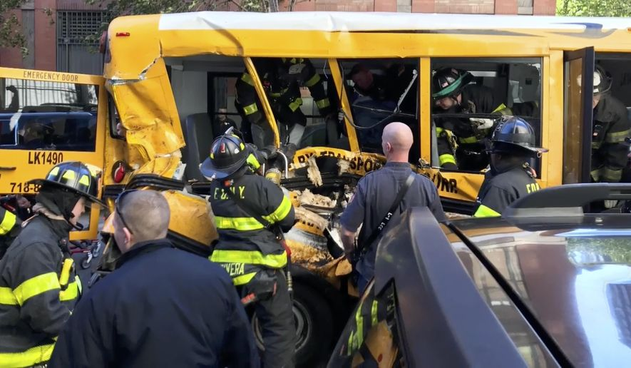 In this Tuesday, Oct. 31, 2017 photo provided by Sebastian Sobczak, emergency personnel work on a school bus after a driver rammed into it in New York. Investigators are working to determine what led a pickup truck driver to plow down people on a riverfront bike path near the World Trade Center, before slamming into the school bus, killing several. (Sebastian Sobczak/BeautifulGoal.Org via AP)