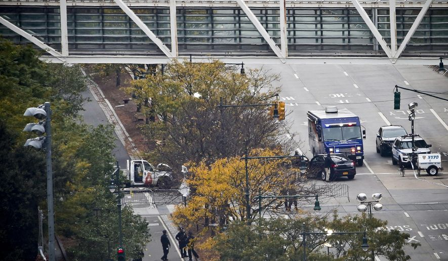 The wreckage of a rental truck used in the deadly attack on Tuesday, is seen near an overpass for Stuyvesant High School, blocking a bike path along the Westside Highway, Wednesday Nov. 1, 2017, in New York. Investigators continue working to determine what led the driver to plow down people on a riverfront bike path near the World Trade Center. (AP Photo/Bebeto Matthews)