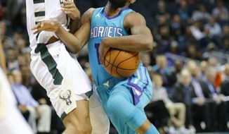 Charlotte Hornets guard Kemba Walker, right, tries to get past Milwaukee Bucks defender Malcolm Brogdon during the first half of an NBA basketball game, Wednesday, Nov. 1, 2017, in Charlotte, N.C. (AP Photo/Jason E. Miczek)