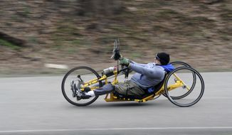 In this March 20, 2017 photo, cyclist Attila Domos, of Squirrel Hill, rides his hand-cranked cycle around the Bud Harris Cycling Track in Highland Park, Pa. Mr. Domos, who was paralyzed in a falling accident in 1993, thinks he stands a good chance to set the official 24-hour hand-cycling world record this coming weekend. (Nate Guidry/Pittsburgh Post-Gazette via AP)