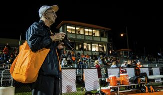 In this Friday, Oct. 20, 2017 photo, Mike Werries, a Springdale High School alumni of the class of 1969, works the sidelines at Veteran's Memorial Field in Springdale, Pa., while taking photographs for the school. The people who make up the Springdale, Jeannette and Gateway school communities say high school football is about life and relationships, pride and tradition. (Shane Dunlap/Pittsburgh Tribune-Review via AP)