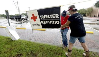 FILE - In this Aug. 25, 2017, file photo, volunteers set up signage outside the Civic Center, where the Red Cross has set up a shelter for those who evacuated their homes due to storm damage in Beaumont, Texas. Texas Gov. Greg Abbott said Wednesday, Nov. 1, 2017 he raised concerns with the American Red Cross following Hurricane Harvey that donated money wasn't getting to people who need it. (Kim Brent/The Beaumont Enterprise via AP, File)