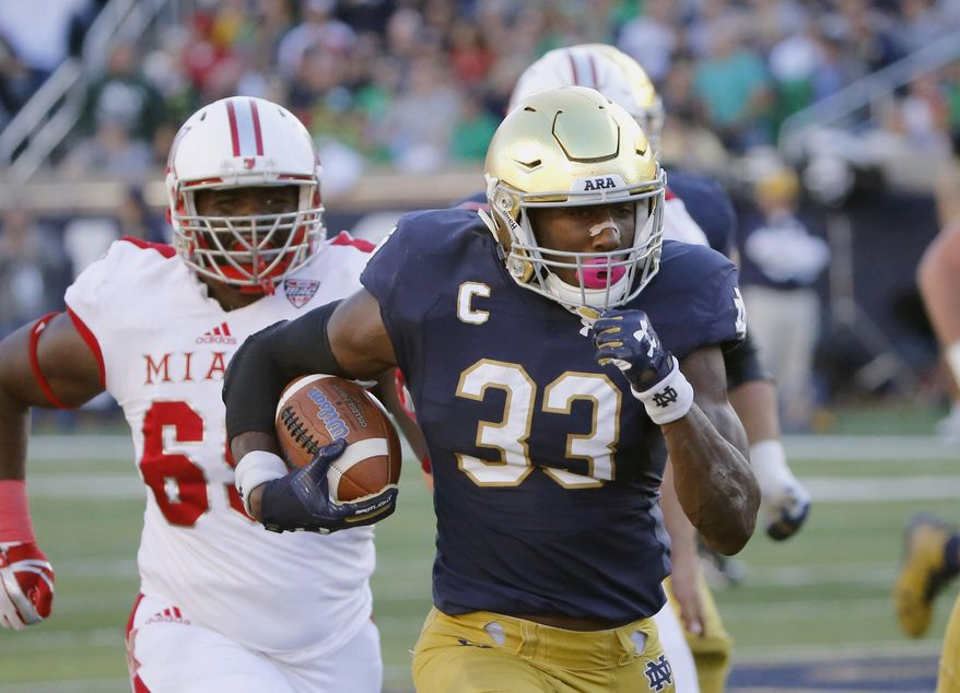 FILE - In this Sept. 30, 2017, file photo, Notre Dame running back Josh Adams (33) heads for the end zone for his second touchdown of the game during the first half of an NCAA college football game against Miami (Ohio) in South Bend, Ind. The noise about a playoff bid and the Heisman Trophy is getting louder around No. 5 Notre Dame as it prepares for the visit from Wake Forest on Saturday, Nov. 4. Junior running back Adams, fifth in the nation in rushing with 1,169 yards, has emerged as a legitimate contender for the Heisman and other postseason awards. (AP Photo/Charles Rex Arbogast, File)