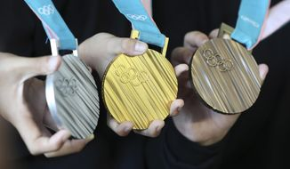 FILE - In this Sep.21, 2017 photo, South Korean athletes pose with the silver, gold and bronze medals, from left, for the Pyeongchang 2018 Winter Olympics during an unveiling ceremony in Seoul, South Korea. Germany would top the medal standings if the Winter Olympics opened tomorrow. This is the statistical analysis from Gracenote Sports, which uses a computer program to forecast Olympic medal winners. (AP Photo/Lee Jin-man)