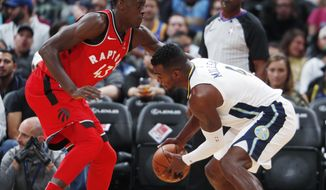 Toronto Raptors forward Pascal Siakam, left, of Cameroon, defends Denver Nuggets forward Paul Millsap as he picks up a loose ball in the first half of an NBA basketball game Wednesday, Nov. 1, 2017, in Denver. (AP Photo/David Zalubowski)