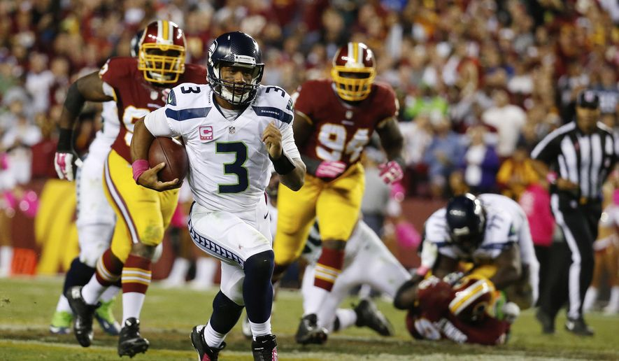 FILE - In this Oct. 6, 2014, file photo, Seattle Seahawks quarterback Russell Wilson (3) scrambles with the ball during the second half of an NFL football game against the Washington Redskins in Landover, Md. After being tormented by Carson Wentz and Dak Prescott, the Redskins' bruised and battered defense faces another test from a mobile quarterback against the Seahawks' Russell Wilson. (AP Photo/Alex Brandon, File) **FILE**