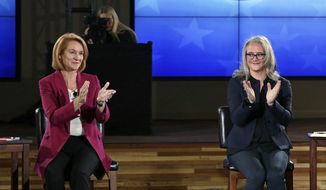 In this photo taken Tuesday, Oct. 24, 2017, Seattle mayoral candidates Jenny Durkan, left, and Cary Moon applaud the audience at the end of a televised debate in Seattle. After 91 years Seattle will elect its second female mayor next week. Voters will choose urban planner Moon or former U.S. attorney Durkan to lead this city dealing with the benefits and headaches of a booming economy for some more than others as e-commerce giant Amazon expands. (AP Photo/Elaine Thompson)