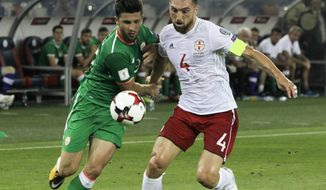 FILE - In this Saturday, Sept. 2, 2017 file photo, Republic of Ireland's Shane Long, left, struggles for the ball with Georgia's Guram Kashia during their World Cup Group D qualifying soccer match at the Boris Paichadze Dinamo Arena in Tbilisi, Georgia. Eight people have been arrested after a far-right group in Georgia gathered to demand a soccer player be kicked off the national team for taking part in a gay rights initiative. The nationalist Georgian March group wants defender Guram Kashia punished for wearing a rainbow armband while captaining Dutch club Vitesse Arnhem in early Oct. 2017. (AP Photo/Shakh Aivazov, file)