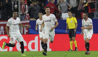 Sevilla's Clement Lenglet, centre, celebrates scoring the opening goal during a Champions League group E soccer match between Sevilla and Spartak Moskva, at the Ramon Sanchez Pizjuan stadium in Seville, Spain, Wednesday, Nov. 1, 2017. (AP Photo/Miguel Morenatti)