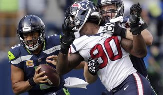 Seattle Seahawks quarterback Russell Wilson, left, keeps the ball as Seattle Seahawks offensive guard Ethan Pocic, right, tries to block Houston Texans outside linebacker Jadeveon Clowney (90) in the second half of an NFL football game, Sunday, Oct. 29, 2017, in Seattle. (AP Photo/Stephen Brashear)