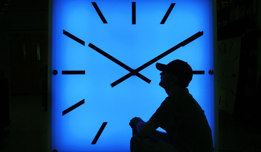 In this Oct. 30, 2008, file photo, Electric Time Company employee Dan Lamoore adjusts the color on a 67-inch square LED color-changing clock at the plant in Medfield, Mass. (AP Photo/Elise Amendola, File)