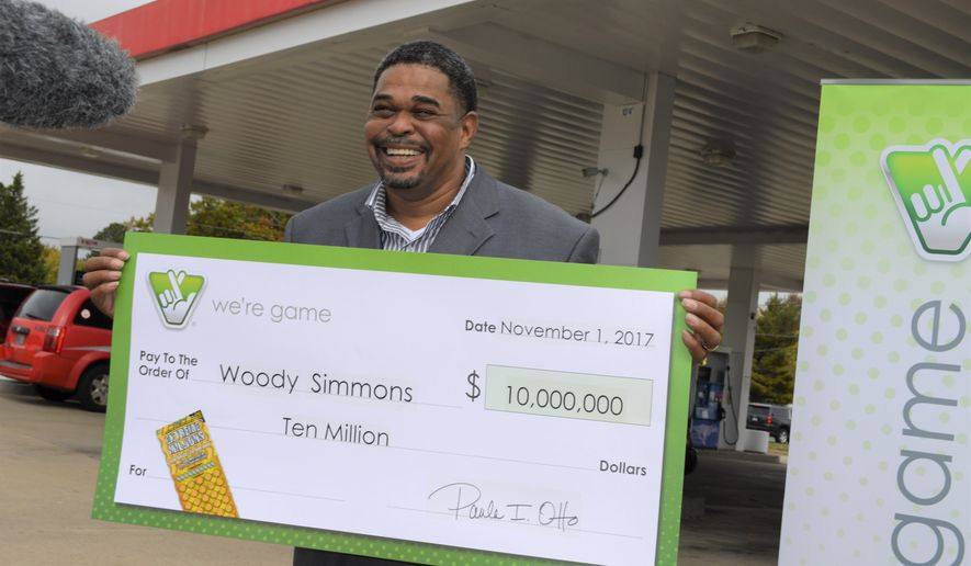 In this image provided by the Virginia State Lottery, Woody Simmons holds a ceremonial check for $10 million dollars in Woodbridge, Va., on Nov. 1, 2017. The U.S. Postal worker bought a Virginia lottery scratch-off ticket last week on impulse, sat in his car _ and screamed. Simmons found he had won $10 million in the Extreme Millions scratch-off game. And then, lottery officials say, Simmons went to his job as if nothing had happened. He kept the ticket in his pocket. (John Hagerty/Virginia State Lottery via AP)