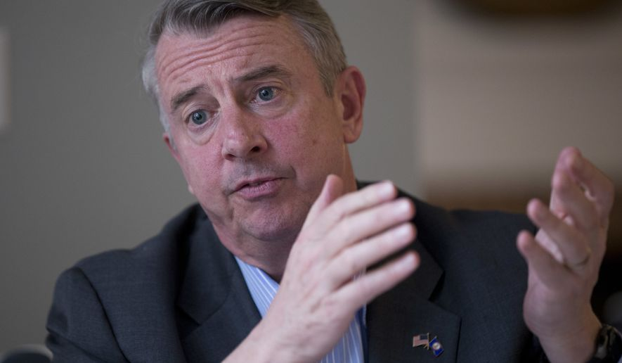 FILE - In this Tuesday March 21, 2017, file photo, Republican gubernatorial candidate, Ed Gillespie, gestures during a kitchen table discussion at a private home in Toano, Va. Political observers say Virginia's closely watched race for governor between Gillespie and Democrat Ralph Northam has become one of the state's most racially charged campaigns in recent memory. (AP Photo/Steve Helber, File)