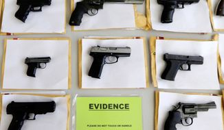 In this July 7, 2014, file photo, Chicago police display some of the thousands of illegal firearms confiscated during the year. In a government report released on Friday, Nov. 3, 2017, the U.S. rate for gun deaths has increased for the second straight year, following 15 years of no real change. (AP Photo/M. Spencer Green, File)