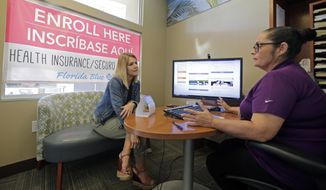 Florida Blue agent Ismaris Crespo, right, explains the different Affordable Care Act enrollment options to Catherine Reviati, left, Thursday, Nov. 2, 2017, in Hialeah, Fla. Health care advocacy groups are making an against-all-odds effort to sign people up despite confusion and hostility fostered by Republicans opposed to former President Barack Obama's signature domestic policy achievement. (AP Photo/Alan Diaz)