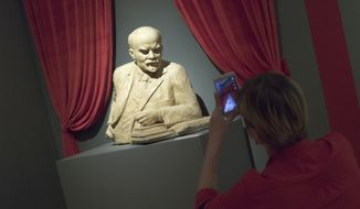 "A woman photographs the sculpture of Soviet founder Vladimir Lenin during the opening of ""Energy of the Dream. entennial of 1917 revolution"" exhibition in Moscow, Russia, on Thursday, Nov. 2, 2017. Russia will mark 100th anniversary of 1917 Bolshevik revolution on Nov. 7, 2017. (AP Photo/Ivan Sekretarev)"