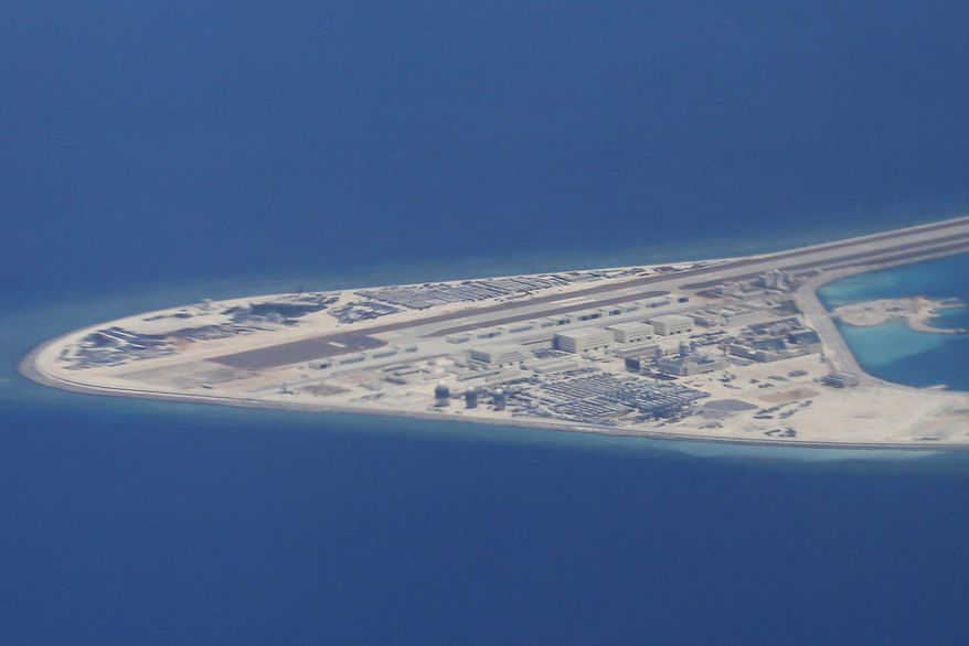 FILE - In this April 21, 2017, file photo, an airstrip, structures and buildings on China's man-made Subi Reef in the Spratly chain of islands in the South China Sea are seen from a Philippine Air Force C-130 transport plane of the Philippine Air Force. Security and trade will loom large during President Donald Trumps first official visit to Asia, which gets underway Sunday, Nov. 5, 2017,  in Japan. Among the world's busiest sealanes, the disputed South China Sea is one of the Asian troublespots, where Trump can showcase American leadership and commitment to the region and edgy allies in a high-profile way. It can also explicitly mirror the lack of it. (AP Photo/Bullit Marquez, File)