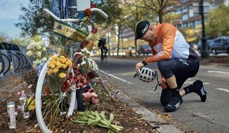 """Eric Fleming, 41, stops by to express his condolences in front of a bike memorial where people leave flowers to remember the victims of the attack on Thursday, Nov. 2, 2017, in New York. A man in a rented pickup truck mowed down pedestrians and cyclists along the busy bike path near the World Trade Center memorial on Tuesday, killing at least eight and seriously injuring others in what the mayor called """"a particularly cowardly act of terror."""" (AP Photo/Andres Kudacki)"""