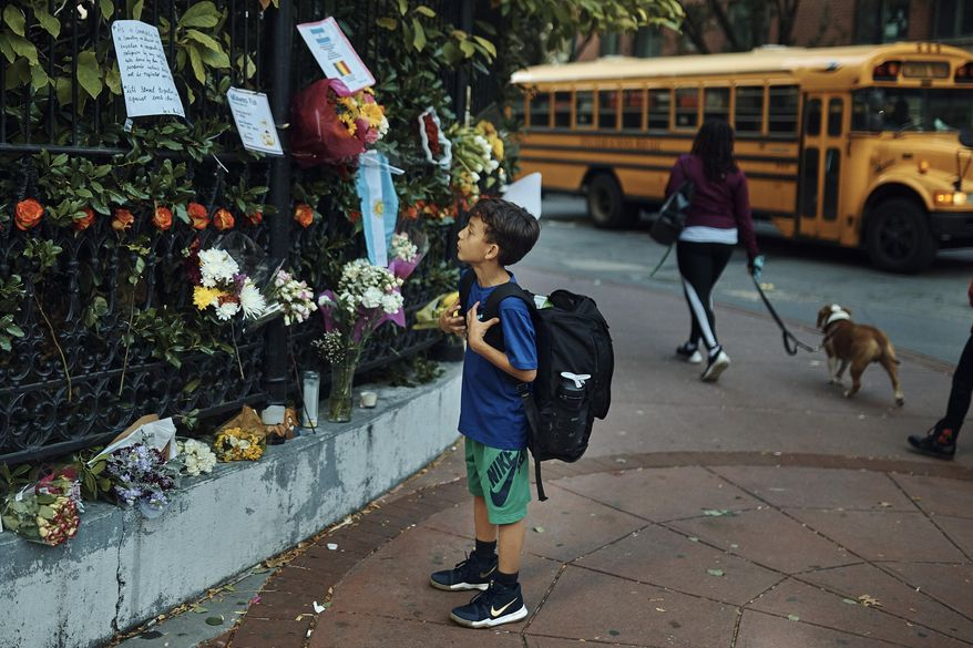 """A child looks at a makeshift memorial to remember the victims of the attack, Thursday, Nov. 2, 2017, near the crime scene in New York. A man in a rented pickup truck mowed down pedestrians and cyclists along the busy bike path near the World Trade Center memorial on Tuesday, killing at least eight and seriously injuring others in what the mayor called """"a particularly cowardly act of terror."""" (AP Photo/Andres Kudacki)"""