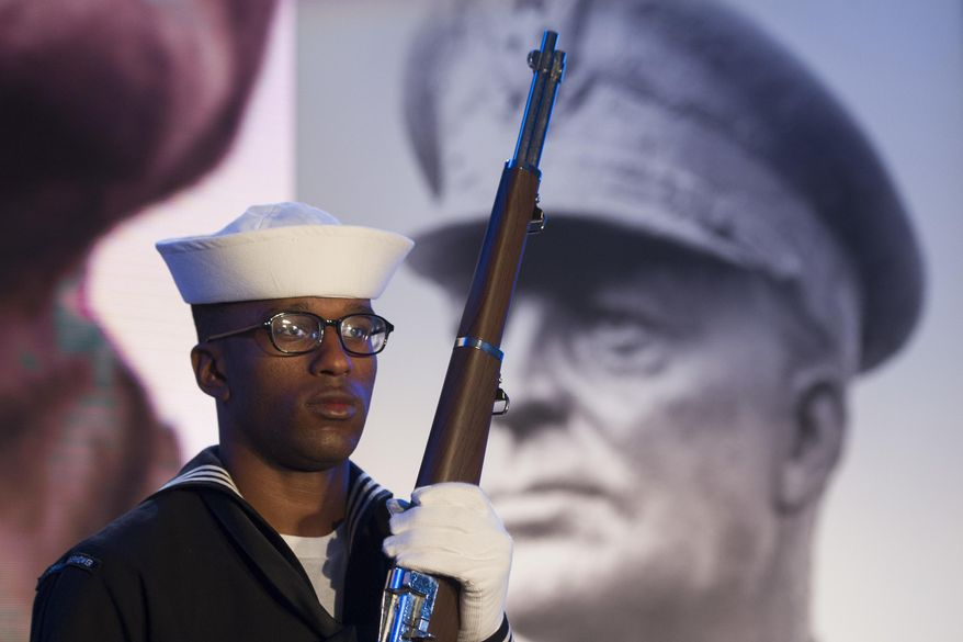 A Navy sailor and member of an honor guard stands in front of a photograph of Gen. Dwight D. Eisenhower during the groundbreaking at the site of the Dwight D. Eisenhower Memorial, in Washington, Thursday, Nov. 2, 2017. (AP Photo/Cliff Owen)
