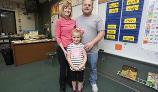 In this Oct. 18, 2017 photo, from left, Sheri Flood, Khloe Frederick and Matt Frederick pose  in Flood's classroom at Williams Elementary School in Mattoon, Ill. Teaching second grade has a been a part of Flood's life for approximately 28 years, and she is retiring at the end of the school year. Khloe is in Flood's final group of students, and her father Matt, was in Flood's first second-grade class of her career in 1988. (Kevin Kilhoffer/Journal Gazette/ Times-Courier via AP)