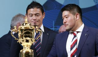 Japan's rugby players Ayumu Goromaru, left, and Kensuke Hatakeyama look at the Webb Ellis Cup during the match schedule announcement for the 2019 Rugby World Cup, in Tokyo Thursday, Nov. 2, 2017. Rugby World Cup organizers announced the match schedule for the Sept. 20-Nov. 2 tournament on Thursday, exactly two years out from the tournament final in Yokohama, near Tokyo. (AP Photo/Shizuo Kambayashi)