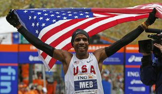 FILE - In this Nov. 1, 2009, file photo, Meb Keflezighi holds a U.S. flag after winning the men's division of the New York City Marathon. Keflezighi is retiring after the New York City Marathon on Sunday, Nov. 5, 2017, capping a career as the only person to win an Olympic medal and New York and Boston titles. (AP Photo/Kathy Willens, File)