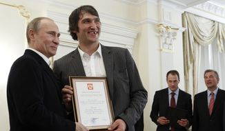 FILE - In this May 29, 2012, file photo, Russian national ice hockey team member Alexander Ovechkin, right, holds a certficate of recognition given to him by President Vladimir Putin, left, in the Novo-Ogaryovo residence outside Moscow.  **FILE**