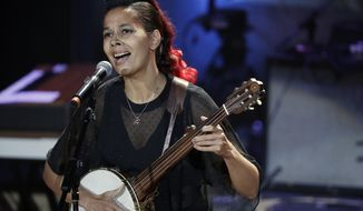 "FILE - In this Sept. 13, 2017 file photo, Rhiannon Giddens performs during the Americana Honors and Awards show in Nashville, Tenn. As a singer, songwriter and instrumentalist, Giddens crosses musical divides. The versatile 40-year-old performer is winning accolades while casting a spotlight on African-American contributions to early American music. This year she was awarded $625,000 ""genius grant"" from the MacArthur Foundation. (AP Photo/Mark Zaleski, File)"