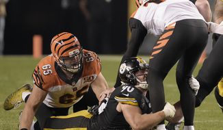 FILE - In this Oct. 22, 2017, file photo, Pittsburgh Steelers outside linebacker T.J. Watt (90) sacks Cincinnati Bengals quarterback Andy Dalton (14) with Bengals offensive guard Clint Boling (65) defending during the second half of an NFL football game in Pittsburgh. Pittsburgh is tied for second in points allowed and is third in sacks. Rookie Watt has helped restore the menace to the pass rush. (AP Photo/Fred Vuich, File)