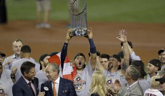 The Houston Astros' Carlos Correa celebrates with the trophy after their win against the Los Angeles Dodgers in Game 7 of baseball's World Series Wednesday, Nov. 1, 2017, in Los Angeles. The Astros won 5-1 to win the series 4-3. (AP Photo/Alex Gallardo)