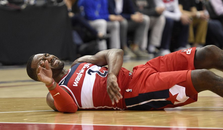 Washington Wizards guard John Wall (2) lies on the court after he was fouled during the second half of an NBA basketball game against the Cleveland Cavaliers, Friday, Nov. 3, 2017, in Washington. The Cavaliers won 130-122.(AP Photo/Nick Wass) **FILE**