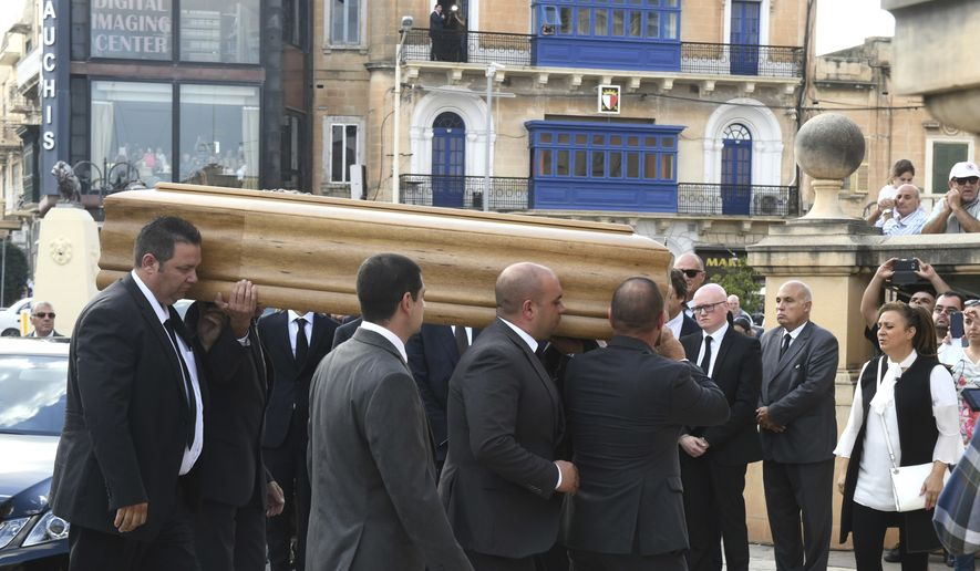 The coffin of Daphne Caruana Galizia, an investigative journalist killed by a car bomb, arrives for the funeral service in Valletta, Malta, Friday, Nov. 3, 2017.  Malta observed a national day of mourning Friday as the Mediterranean island's largest church hosted funeral services for the journalist. (AP Photo/Jonathan Borg)