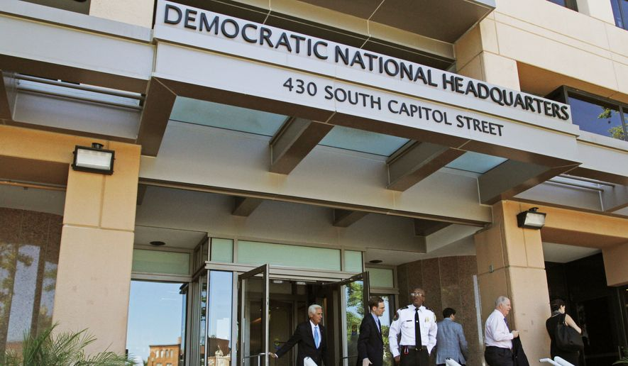 In this June 14, 2016 file photo, people stand outside the Democratic National Committee headquarters in Washington. The DNC on Feb. 14, 2018 laid out its criteria for how 2020 primary candidates in an already-crowded field will be selected for televised debates. (AP Photo/Paul Holston, File) **FILE**