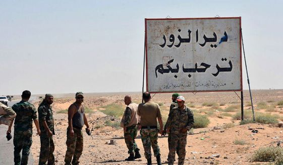 """FILE - This file photo released Sept. 3, 2017, by the Syrian official news agency SANA, shows Syrian troops and pro-government gunmen standing next to a sign in Arabic which reads, """"Deir el-Zour welcomes you,"""" in the eastern city of Deir el-Zour, Syria. Syrian state media say the army has liberated the eastern city of Deir el-Zour from the Islamic State group. Friday's report says the military is now in full control of the long contested city. (SANA via AP, File)"""